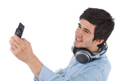 Male student taking photo with mobile phone. On white background Stock Photography