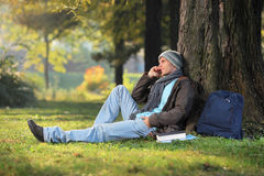 A male student talking on a phone. Seated on a grass in the city park Royalty Free Stock Photography