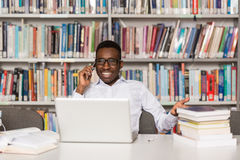 Male Student Talking On The Phone In Library. African Male Student Talking On The Phone In Library - Shallow Depth Of Field Royalty Free Stock Photos
