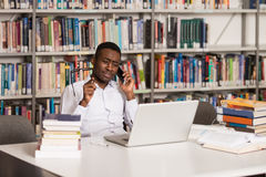 Male Student Talking On The Phone In Library. African Male Student Talking On The Phone In Library - Shallow Depth Of Field Stock Photos