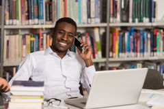 Male Student Talking On The Phone In Library. African Male Student Talking On The Phone In Library - Shallow Depth Of Field Royalty Free Stock Photography
