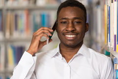 Male Student Talking On The Phone In Library. African Male Student Talking On The Phone In Library - Shallow Depth Of Field Royalty Free Stock Images