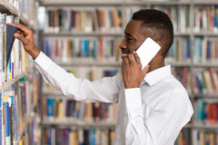 Male Student Talking On The Phone In Library. African Male Student Talking On The Phone In Library - Shallow Depth Of Field Stock Photo