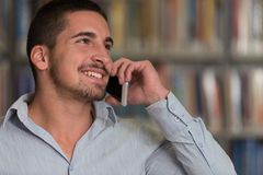 Male Student Talking On The Phone In Library. Shallow Depth Of Field Royalty Free Stock Images