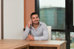 Male Student Talking On The Phone In Library. Shallow Depth Of Field Royalty Free Stock Image