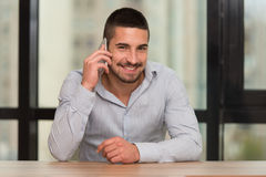 Male Student Talking On The Phone In Library. Shallow Depth Of Field Royalty Free Stock Photography