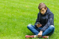 Male student talking on a phone seated on a grass in the city park. Outdoor Stock Image