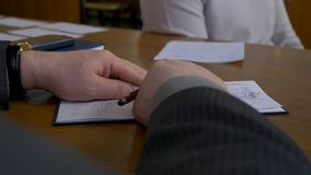 Male student with a teacher in classroom. Teacher writes the assessment in the gradebook.  Stock Image