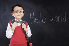 Male student with text Hello World. Male elementary school student standing in the class while wearing uniform and glasses with text Hello World on the Stock Images