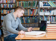 Male student  texting on the phone in the university library.  Stock Photos