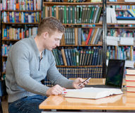 Male student texting on the phone in the university library Stock Images