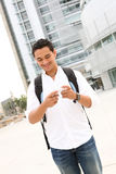Male Student Texting at School. A handsome young student texting at college university Royalty Free Stock Images