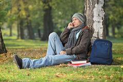 Male student thinking, seated by a tree in park. Male student thinking seated by a tree outdoors Royalty Free Stock Photo