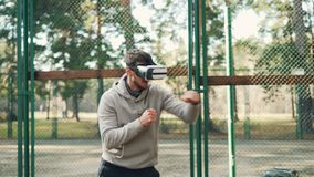 Male student is training in park wearing virtual reality glasses and boxing alone enjoying activity and modern. Technology. Sports, millennials and cool gadgets stock footage