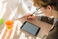 Male student in tweed jacket doing homework assignment at cafe during lunch time. Handsome teenage person in reading eyeglasses works with tablet pc and books in Royalty Free Stock Photo