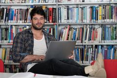 Male Student Typing on Laptop in the University Library. In the Library - Handsome Male Student With Laptop and Books Working in a High School - University Stock Photo
