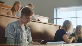 A male student in a University auditorium listens to music in white headphones during a break without paying attention. To others. A lot of people in the stock video