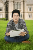 Male student uses tablet at school yard. Portrait of a young male student sitting on the school yard while using a digital tablet Stock Photography