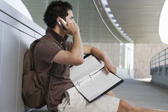 Male Student Using Cell Phone. Side view of male student with file using cell phone Stock Photo