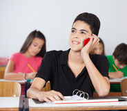 Male Student Using Cellphone In Classroom. Teenage male student looking away while using cellphone at desk in classroom Stock Images