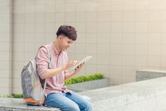 Male student using digital tablet in college campus.  Stock Photos