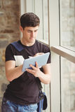 Male student using digital tablet in college. Male student using digital tablet while leaning on window in college Royalty Free Stock Photos
