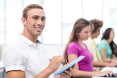 Male student using digital tablet in computer class. Side view of male student using digital tablet in computer class Royalty Free Stock Image