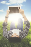 Male student using a digital tablet. Image of young male student lying on the meadow while holding and touching a digital tablet screen Royalty Free Stock Image