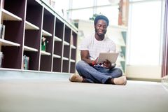 Male Student Using Digital Tablet In Library. Full length of young male student using digital tablet while sitting on floor at library Royalty Free Stock Photography
