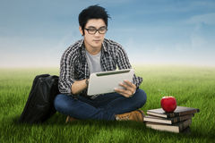 Male student using digital tablet outdoors. Handsome student sitting on the grass while using tablet Royalty Free Stock Image