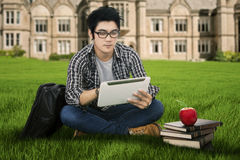 Male student using digital tablet outdoors 1. Handsome student sitting on the grass while using tablet Royalty Free Stock Photos