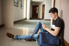 Male student using digital tablet sitting by wall. In corridor at college Royalty Free Stock Images