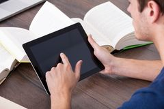 Male student using digital tablet. Male Student Surrounded By Books Using Digital Tablet Royalty Free Stock Image