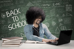 Male student using earphone in the classroom. Male college student using a laptop and earphone while sitting in the classroom with scribble on the chalkboard Royalty Free Stock Image