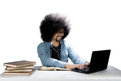 Male student is using a headset. Picture of an Afro male college student using a headset while studying with a laptop and books on the desk Royalty Free Stock Photos