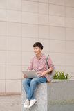 Male student using laptop in college campus.  Stock Images