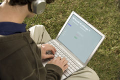 Male student using a laptop outdoors Stock Photo