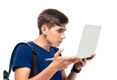 Male student using laptop. Male student standing and using laptop isolated on a white background Royalty Free Stock Image