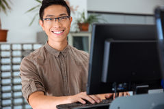 Male student using personal computer in university. Portrait of a happy male student using personal computer in university Stock Images