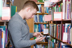 Male student using smartphone  in college library.  Royalty Free Stock Photo