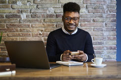 Male student using wifi zone and modern devices with smile on face. Portrait of cheerful international male freelancer in spectacles looking for camera and Royalty Free Stock Photo