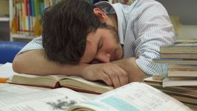 Male student wakes up at the library. Attractive male student waking up at the library. Close up of brunette caucasian guy continuing to study the textbook Royalty Free Stock Images