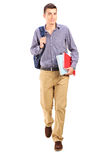 Male student walking with backpack. Full length portrait of a male student walking with backpack isolated on white background Stock Photo