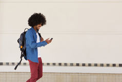 Male student walking with bag and mobile phone. Side portrait of a male student walking with bag and mobile phone Royalty Free Stock Photos