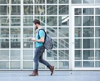 Male student walking on campus with bag and mobile phone. Side view portrait of a male student walking on campus with bag and mobile phone Royalty Free Stock Image