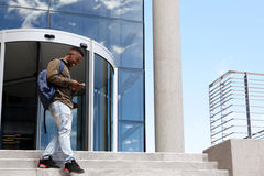 Male student walking on campus with mobile phone. Portrait of male student walking on campus with mobile phone Stock Images