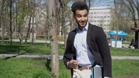 Modern student walking in park with laptop in hand. Male student walking in park with laptop and papers in hand.Fortunate man has big smile and dimples on Stock Images