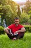 Male student sitting with book on green grass. Male student wearing t-shirt sitting on green grass with book and looking at the camera Stock Image