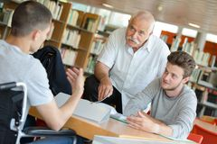 Male student in wheelchair in library Stock Photo