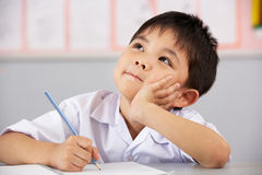 Male Student Working At Desk In Chinese School Royalty Free Stock Photos